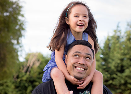 Smiling father with daughter on shoulders.